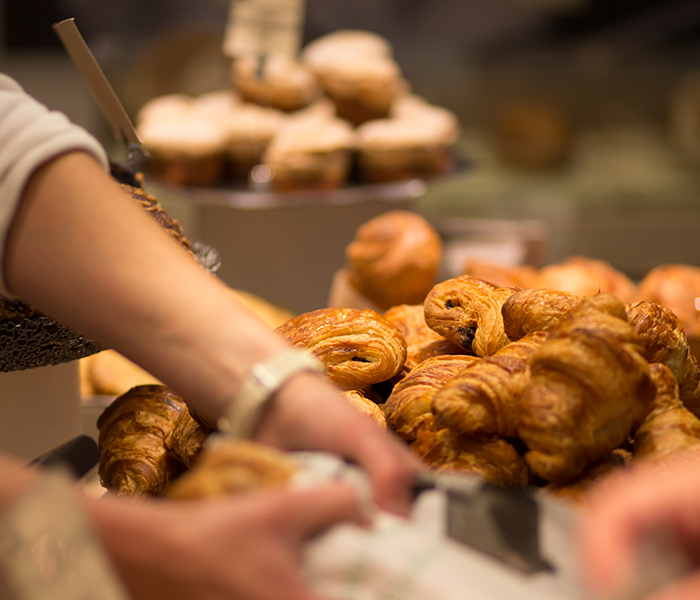 A French woman picks up a roll from a bakery display