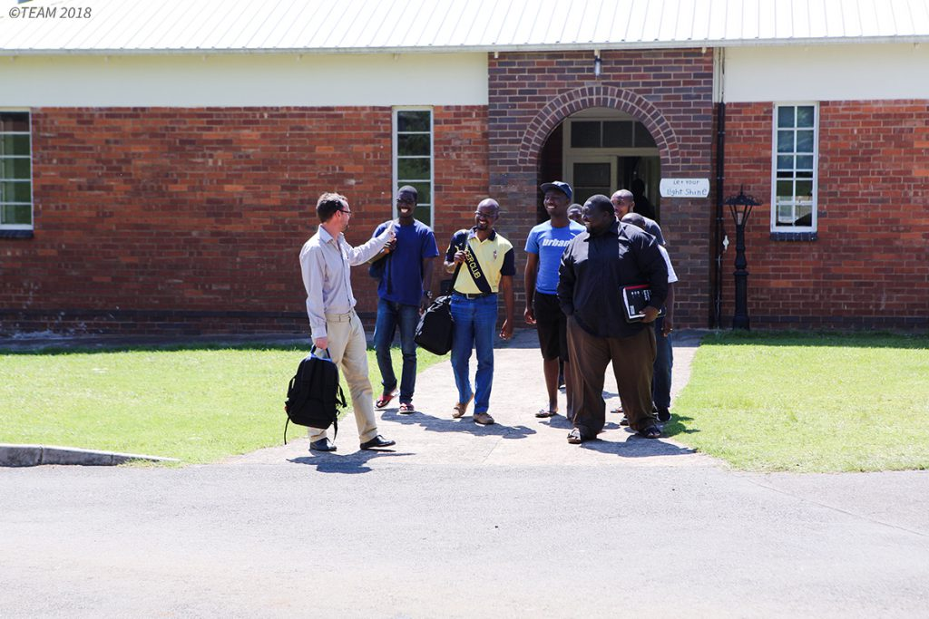 Students and missionary stand outside of school