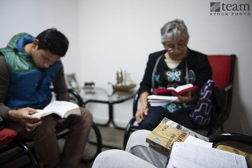 A group of people in Mexico sit and read their Bibles together.