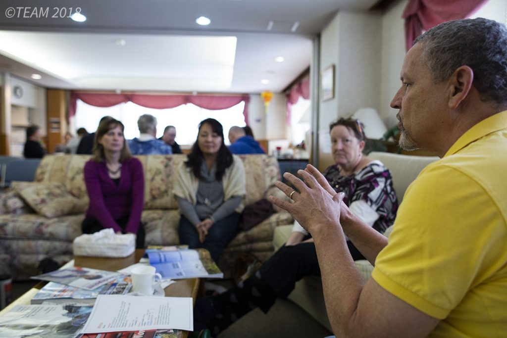 A group of missionaries talk with each other, which can be helpful in language learning.