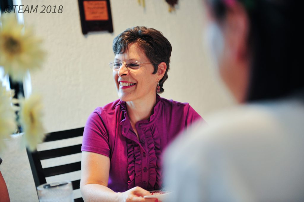 A missionary woman over 50 speaks with other people.