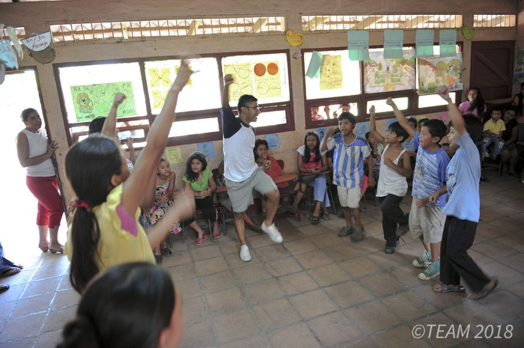A camp leader dances with a group of kids at Vacation Bible School