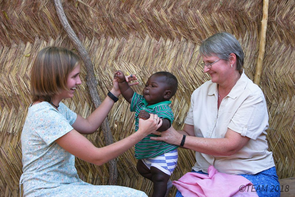 A missionary and her daughter in Africa play with a small child,