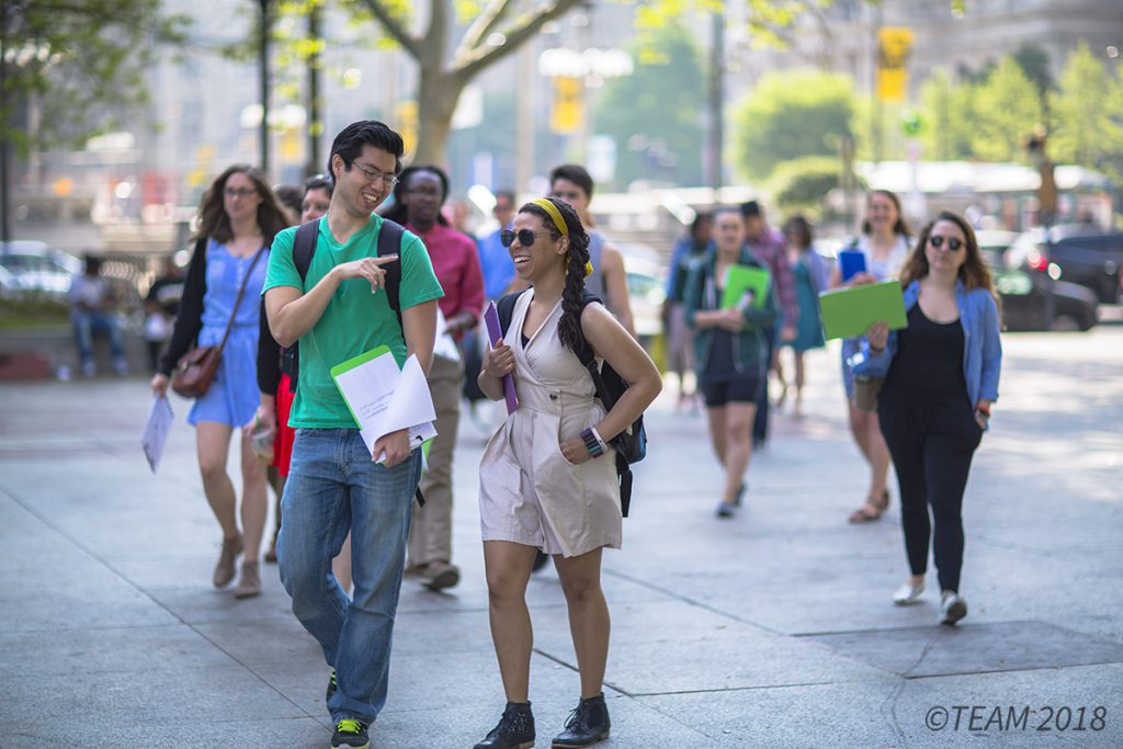 College age students talk while walking around downtown Philadelphia.