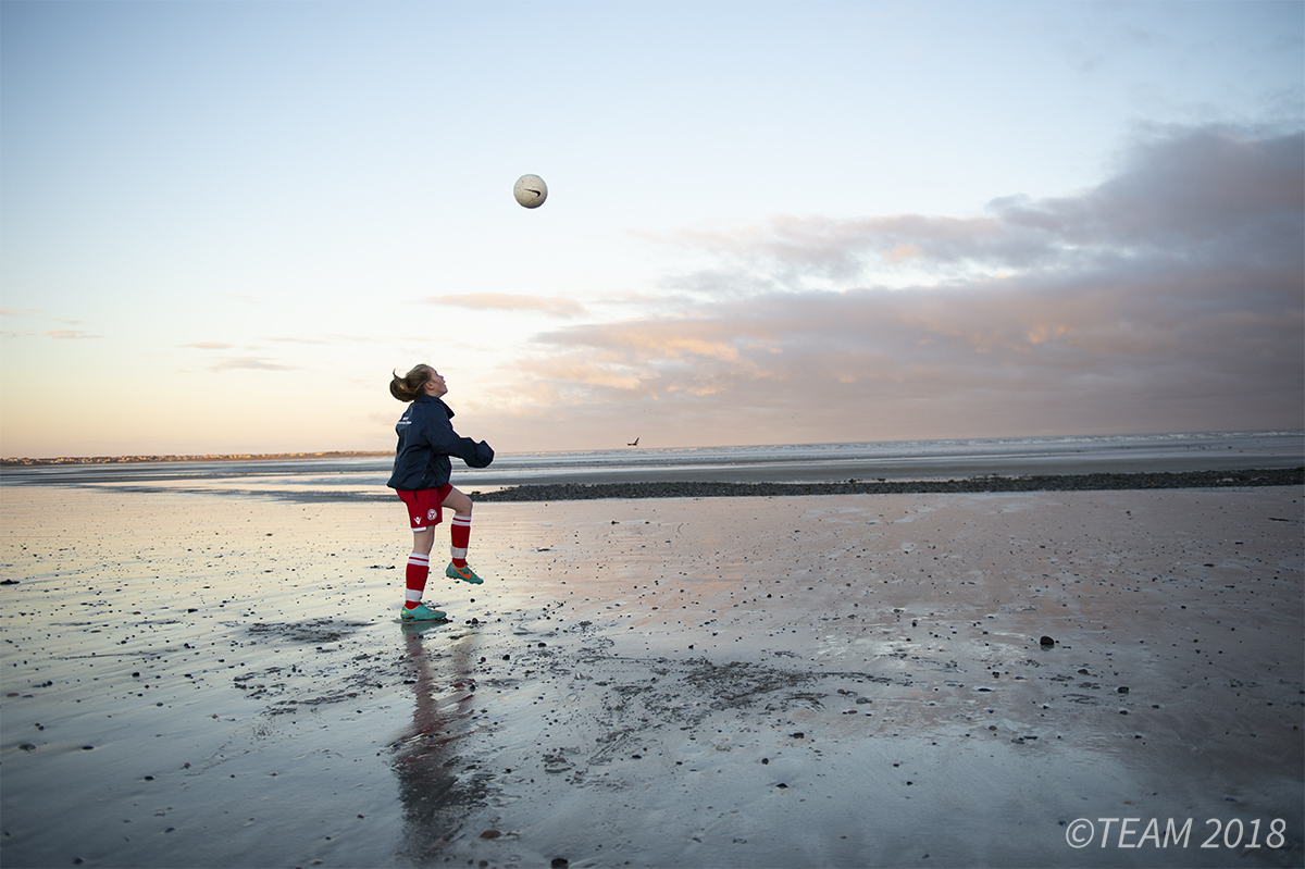 A girl plays with a soccer ball on the beach at sunset