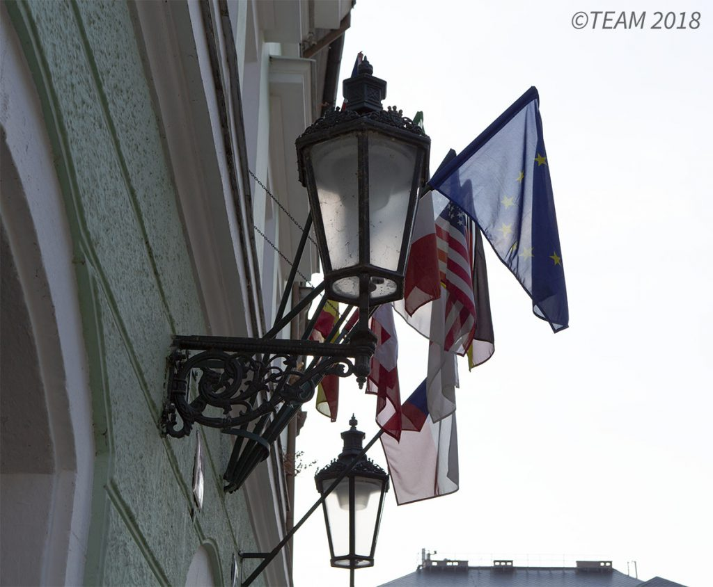 A lamp post in France has several different countries' flags hanging by it.