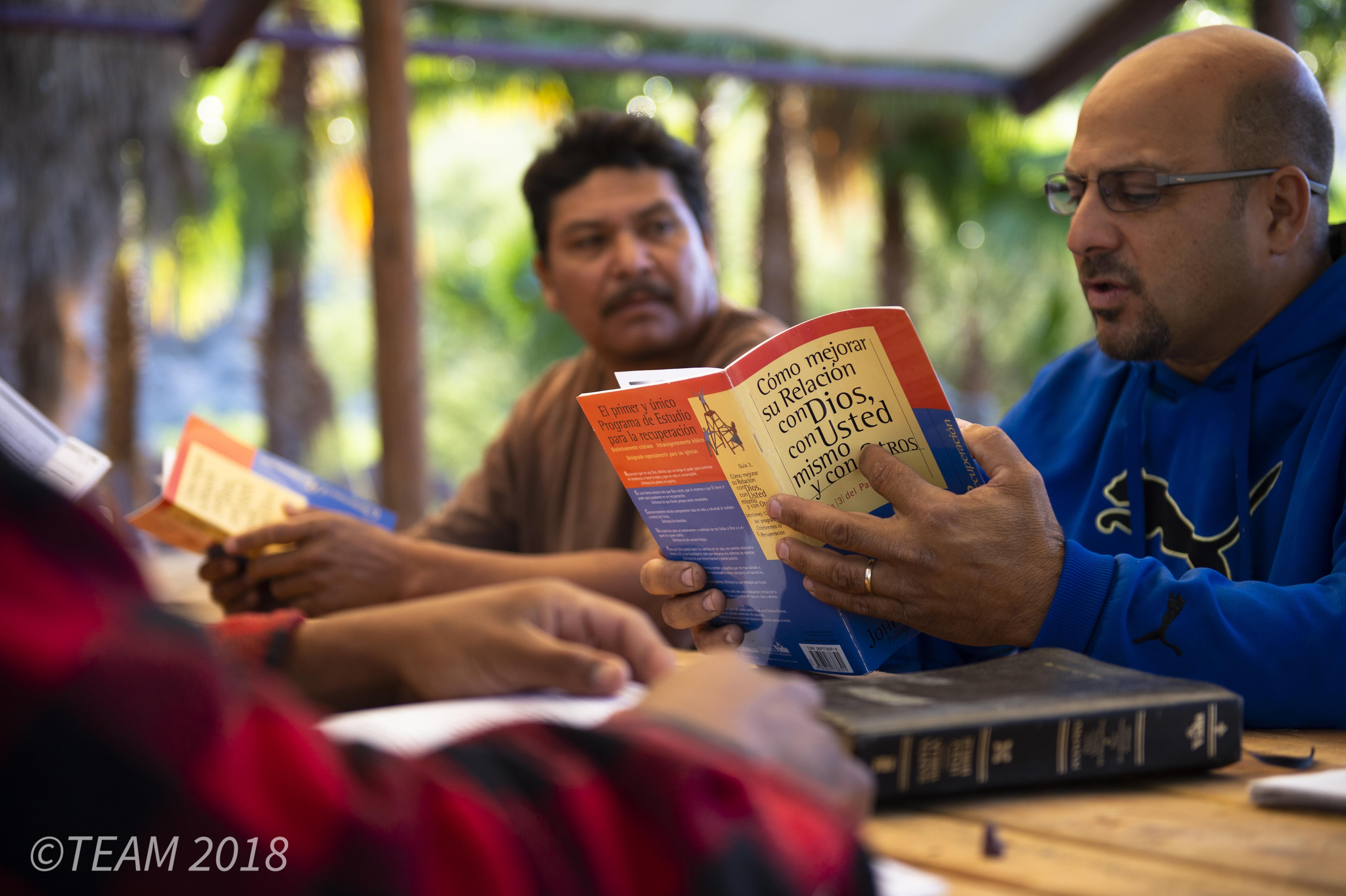 A man reads a book at a Bible study