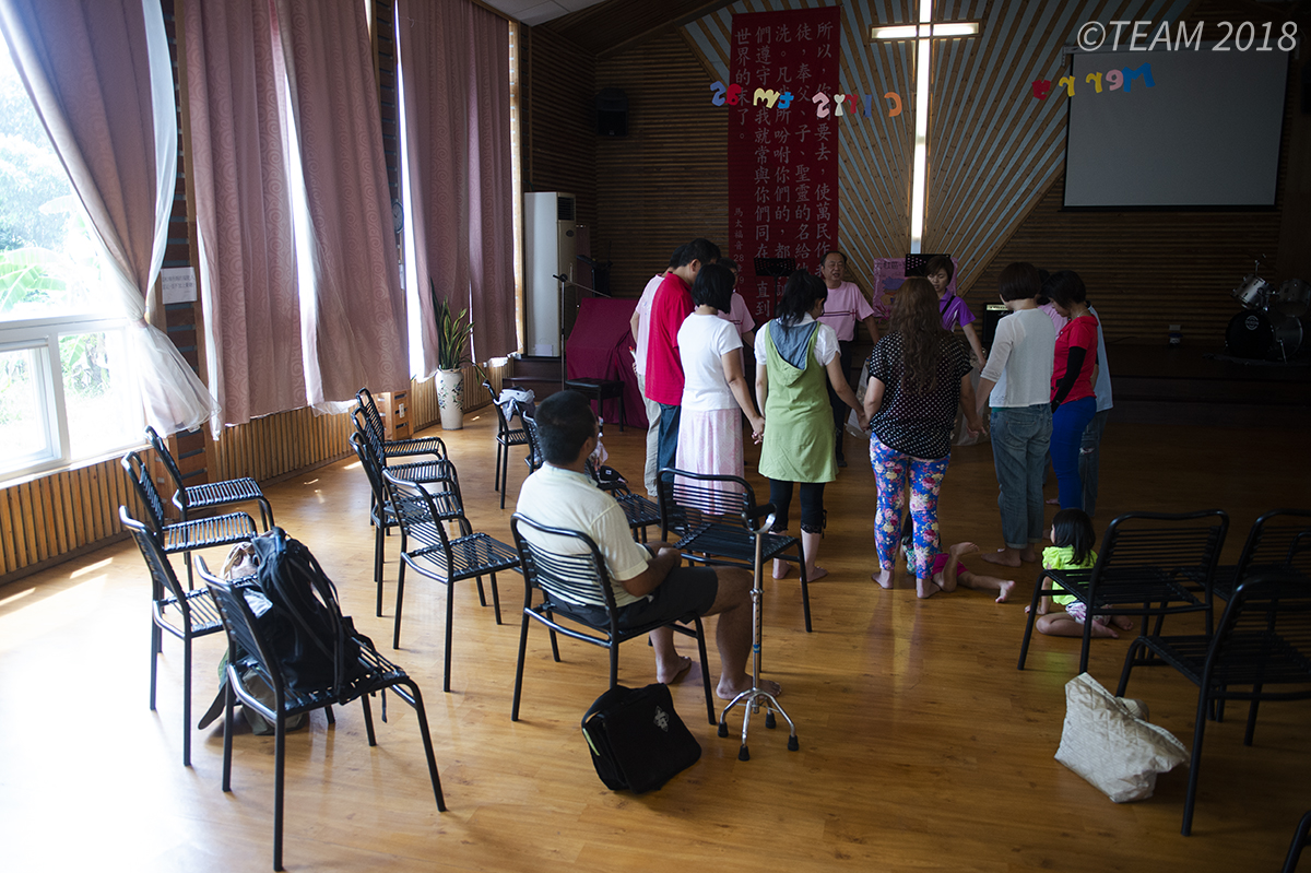 People pray together in a church in a different culture