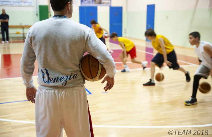 A basketball coach stands with a basketball on his hip as he watches campers run basketball drills.