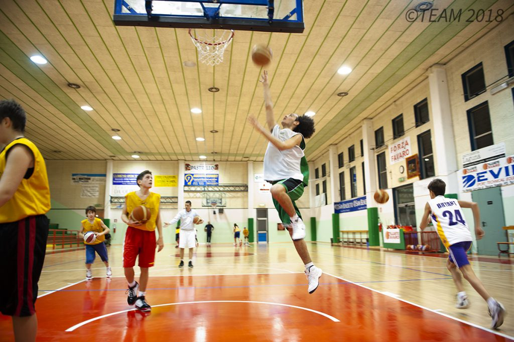 A participant at basketball camp jumps up to make a basket