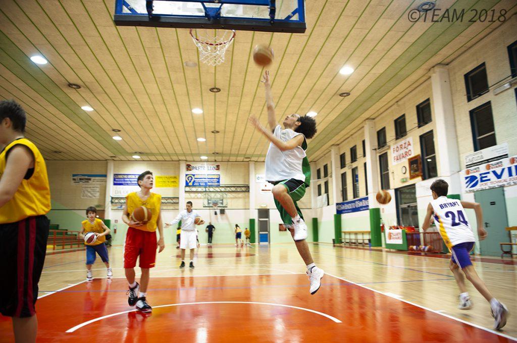 A participant at basketball camp jumps up to make a basket