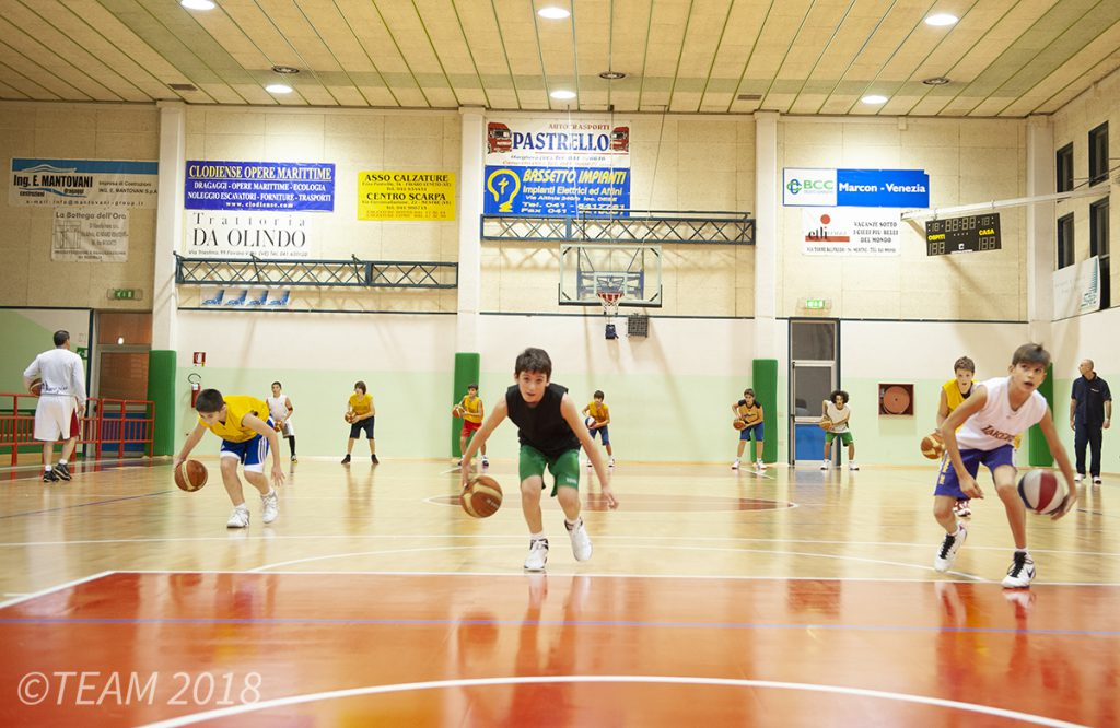 A group of kids at Push the Rock camp practice their basketball skills by dribbling the ball across the court.
