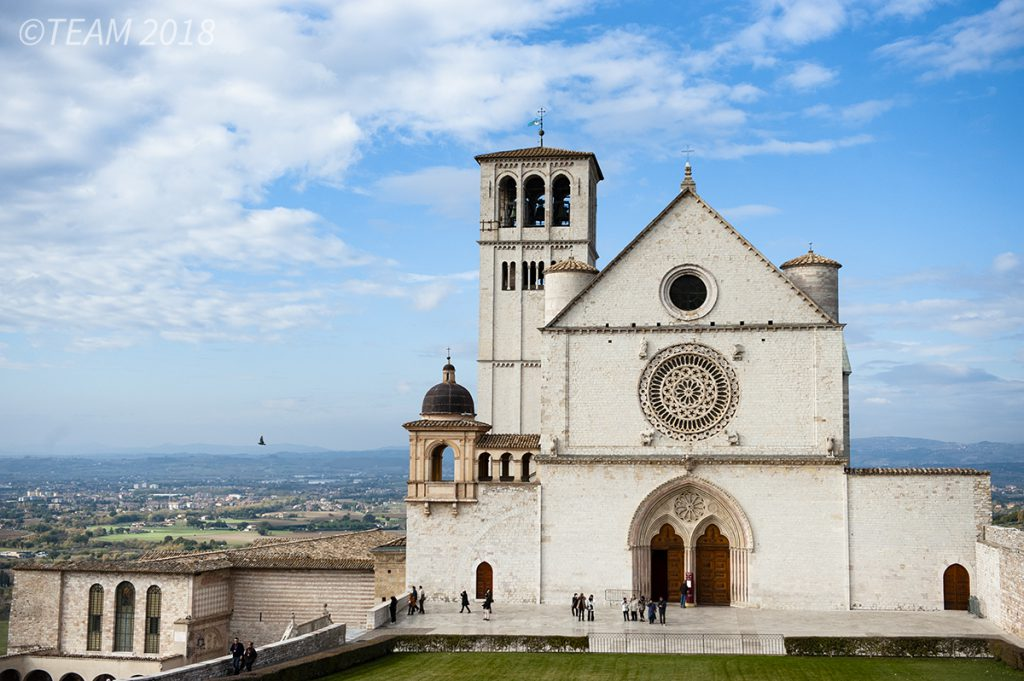 A large, beautiful Cathedral in Italy sits overlooking the city below.