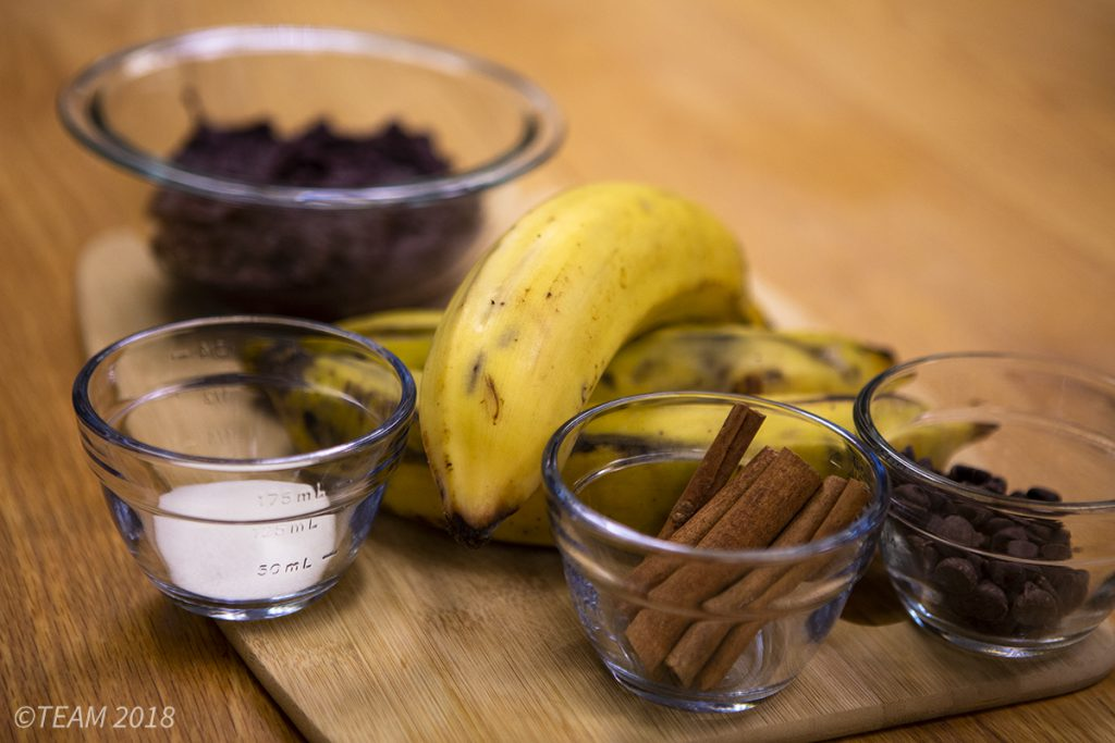 All of the ingredients are set out on a cutting board: plantains, sugar, cinnamon, chocolate, and black beans.