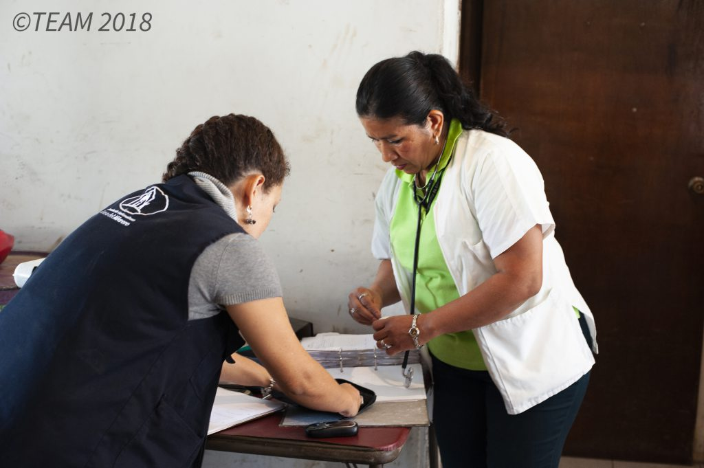 A missionary serving as a nurse reads the chart of one of her patients.
