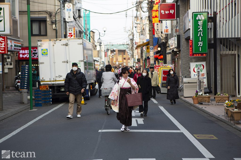 This street in Japan shows how Japanese culture looks very different from American culture. The people are dressed differently, signs are in Japanese, and there are many colorful signs.