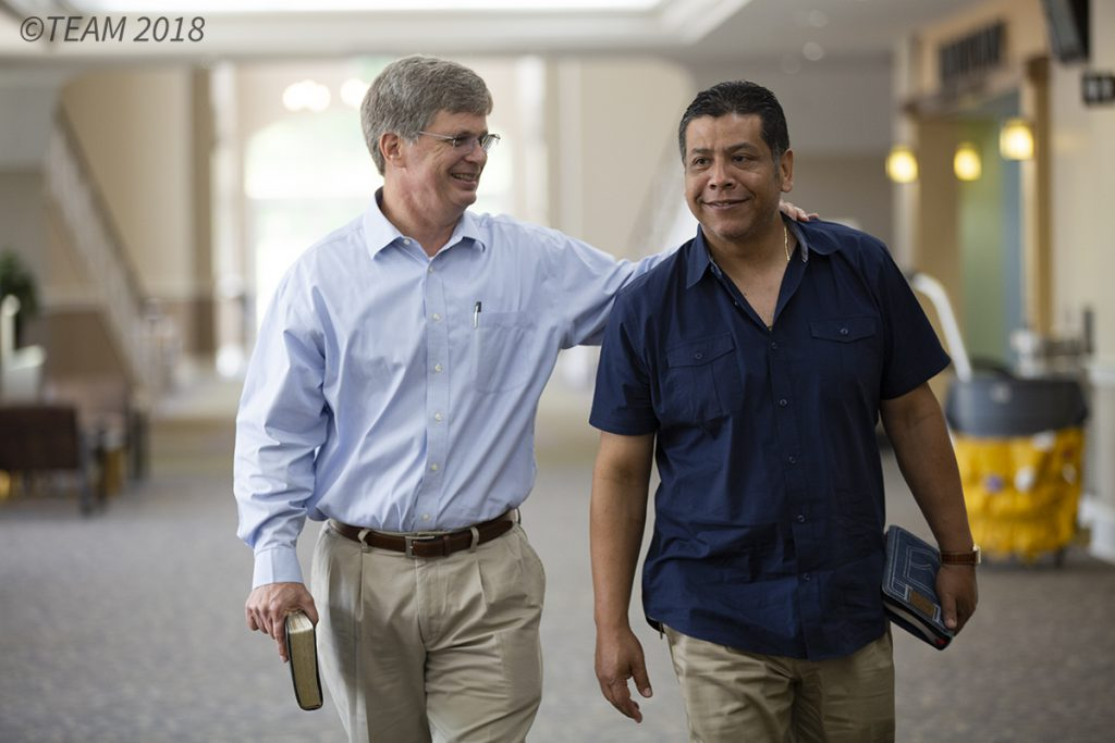 An American missionary and a Hispanic member of the church walk together carrying Bibles.