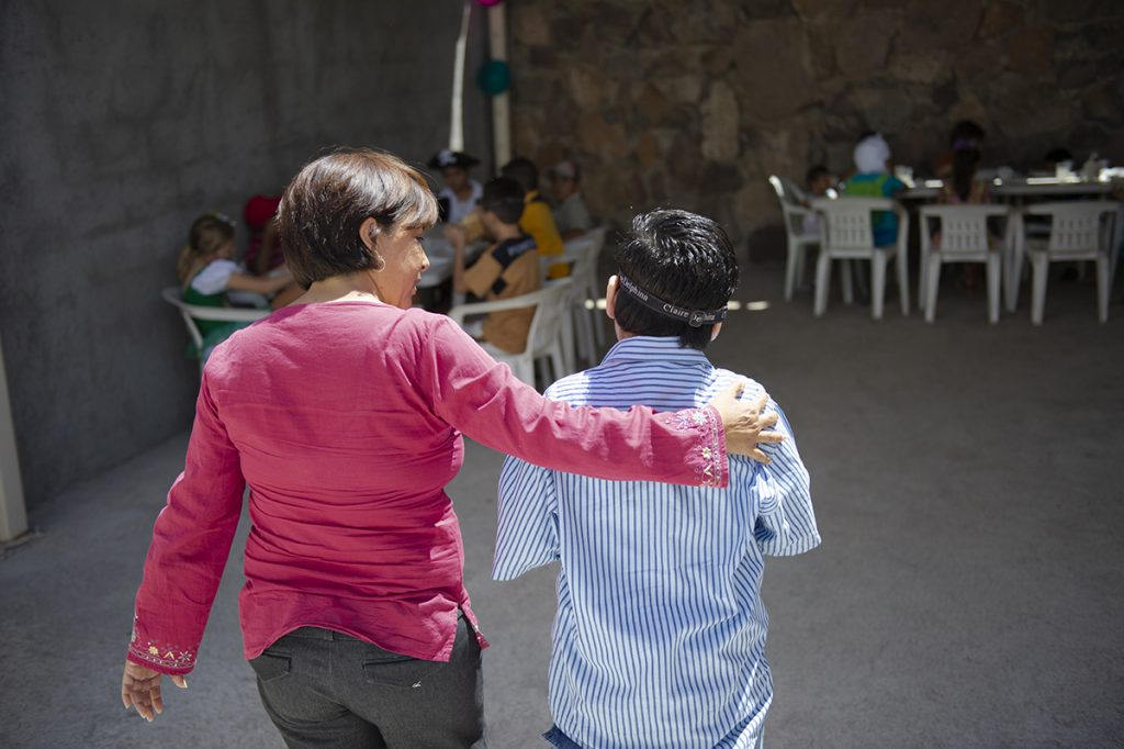 A woman in Mexico puts her arm around her son.