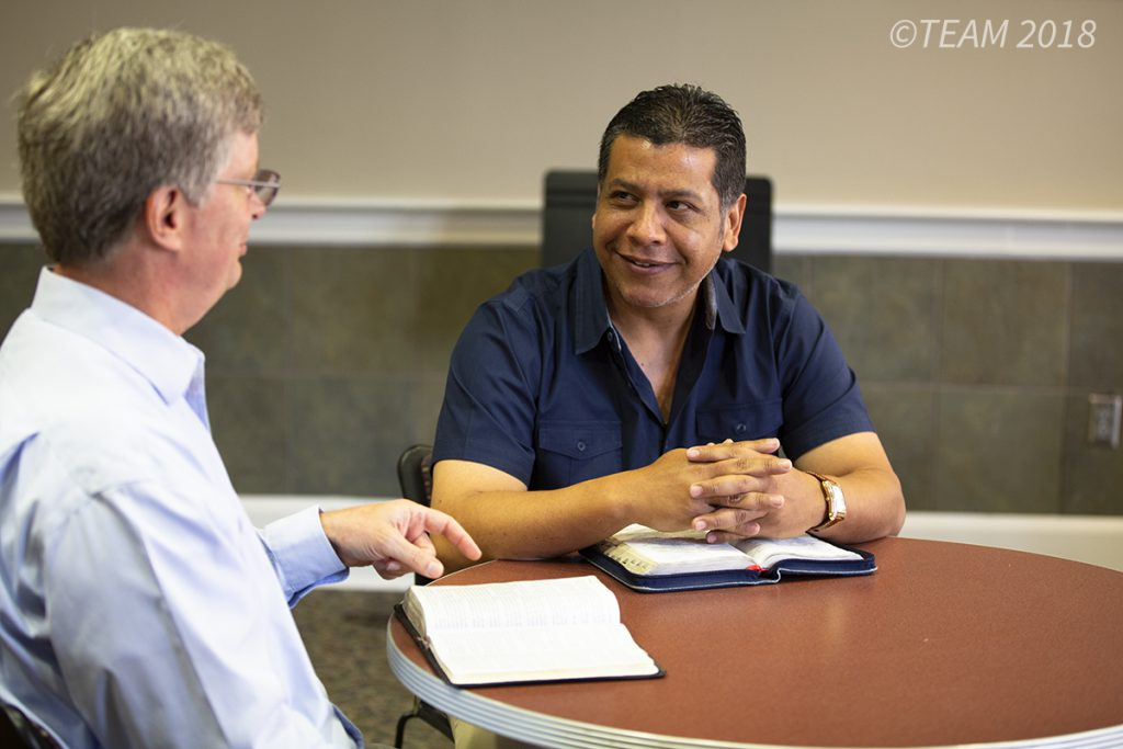 Julio and Keith Moore sit at a table and study the Bible together.