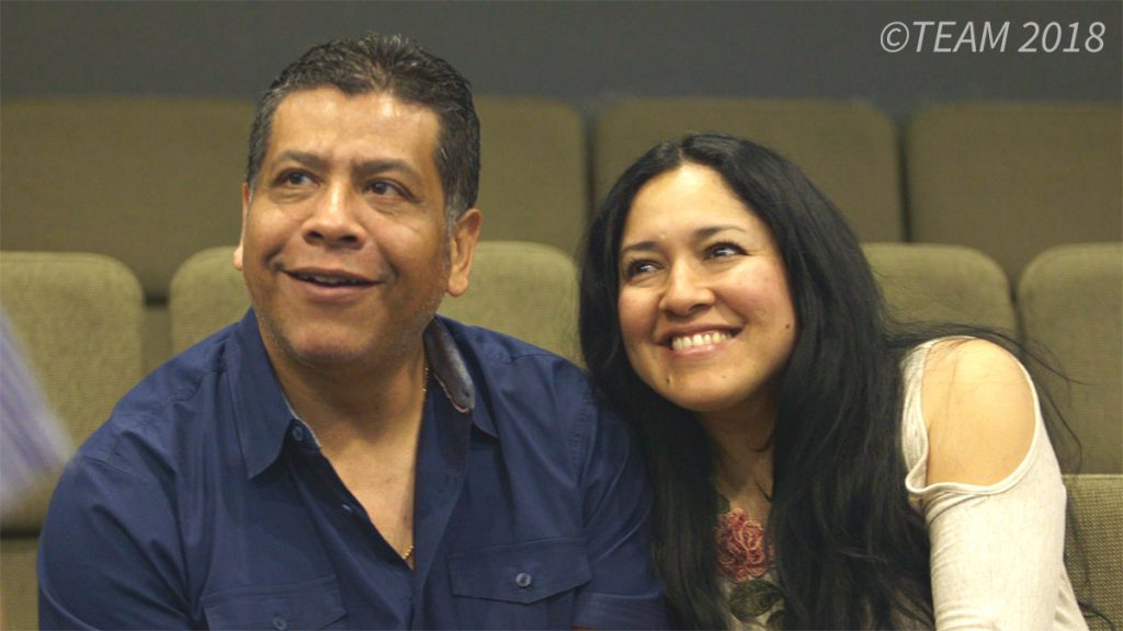 Julio and Libia sit together in church at Impacto Charlotte