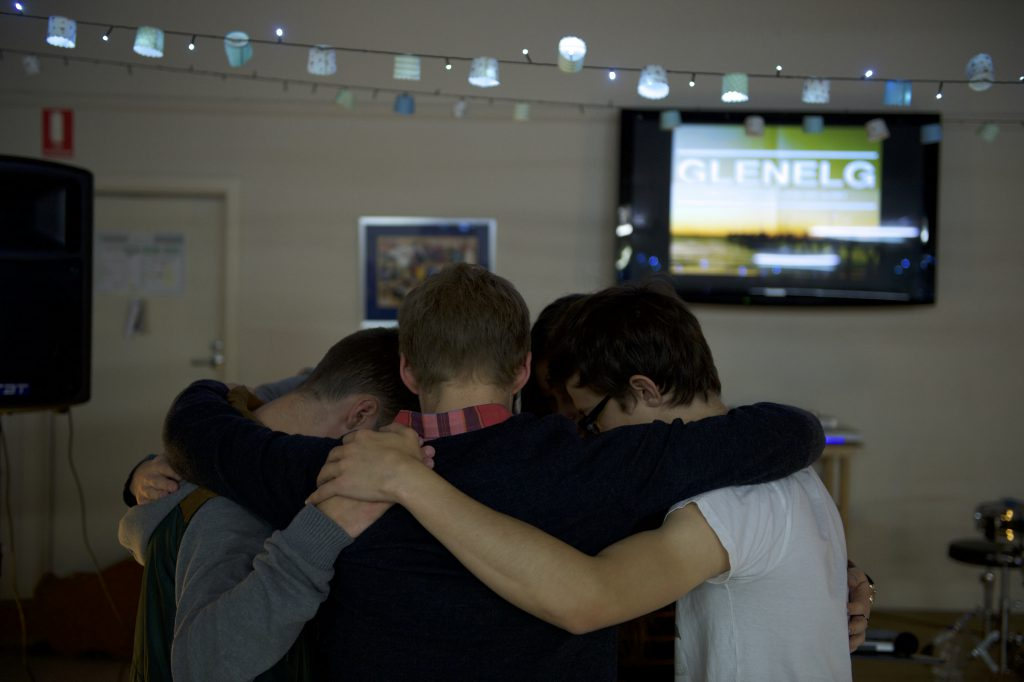 A group of young men huddle together to pray.