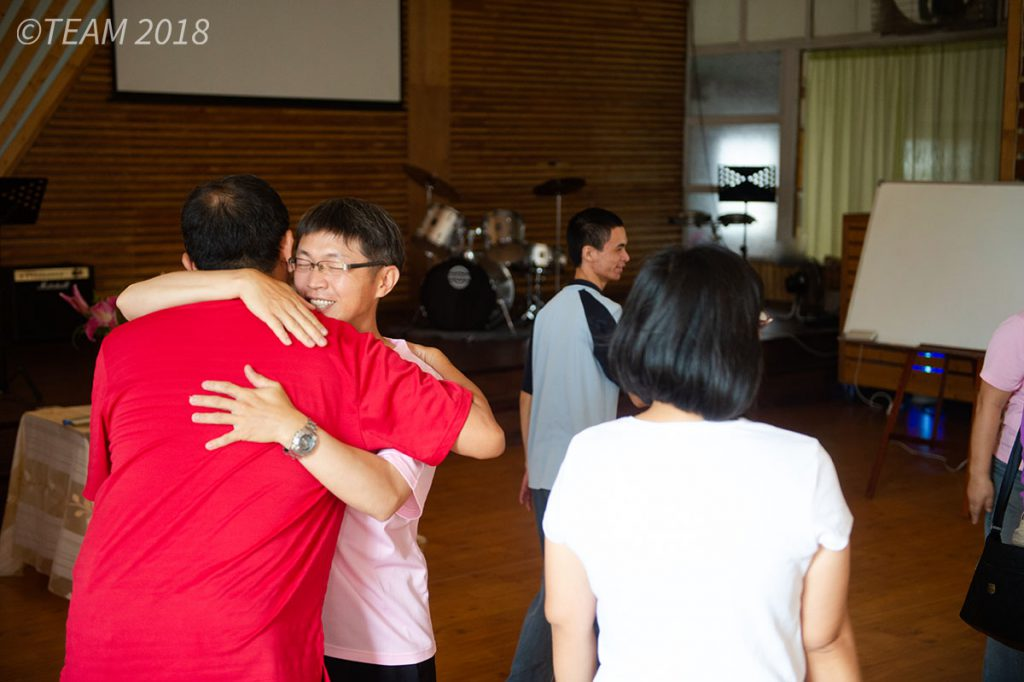 A church member embraces his pastor in a hug.