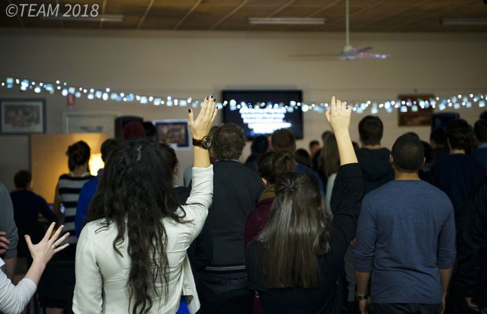 People raise their hands in worship at a church ministry happening in Australia