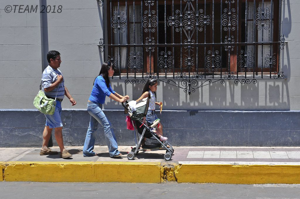 A mom pushes her son down the street in a stroller while her daughter walks by the stroller and the father walks behind the mother.