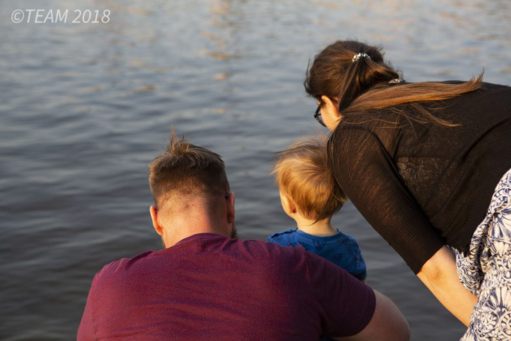 A mother and a father look out over a lake with their son
