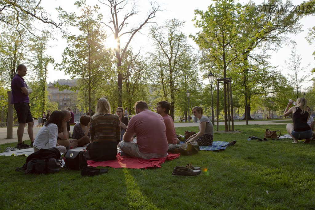 A group of missionaries sit on a blanket in the park to talk.