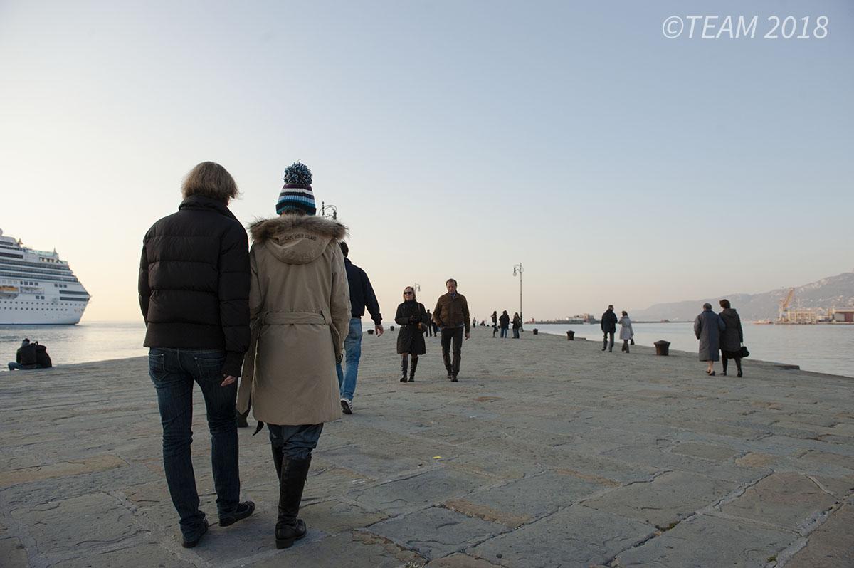 Two Italian women walk along the waterline.