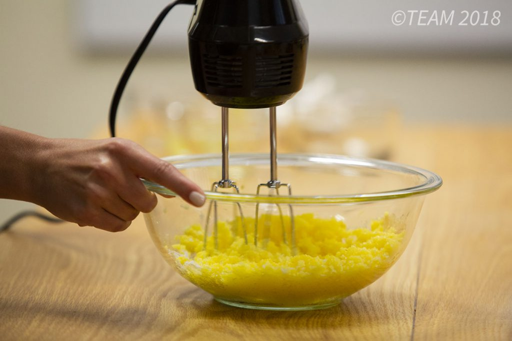 The baker uses a hand mixer to combine the ingredients.
