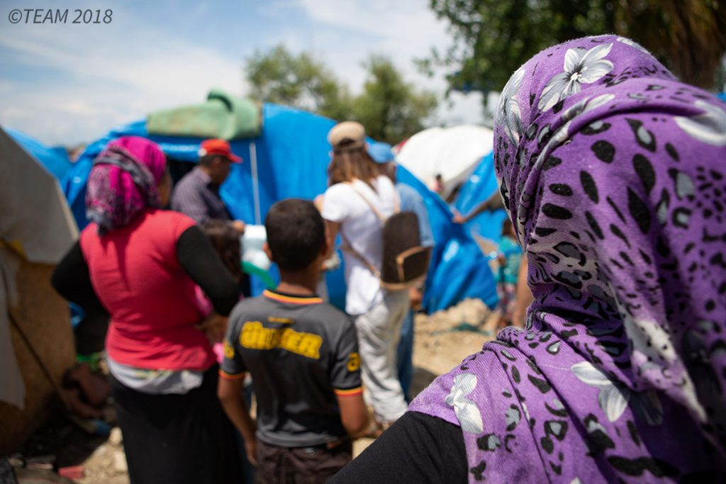 A group of refugee women and children stand together at the refugee camp
