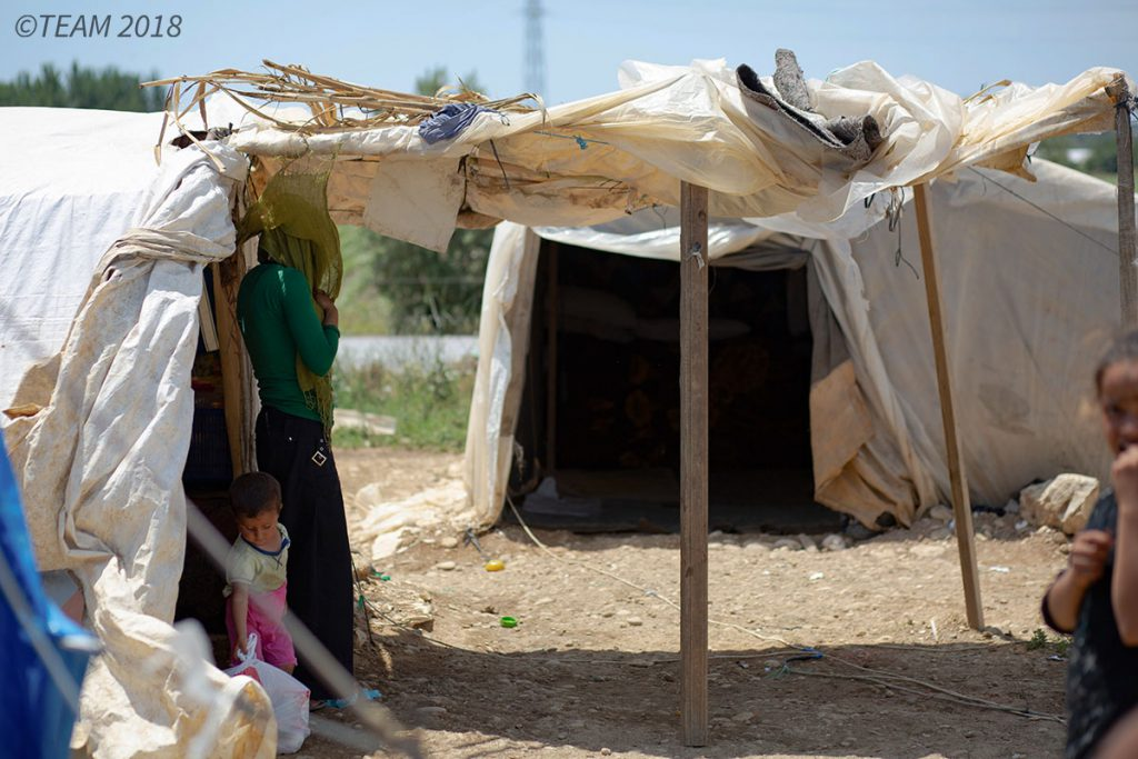 A refugee mother and her child stand underneath a tent at the refugee camp