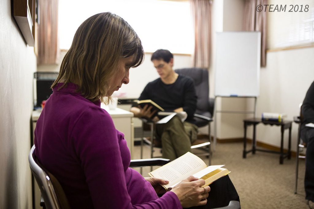 A woman sits and reads her Bible