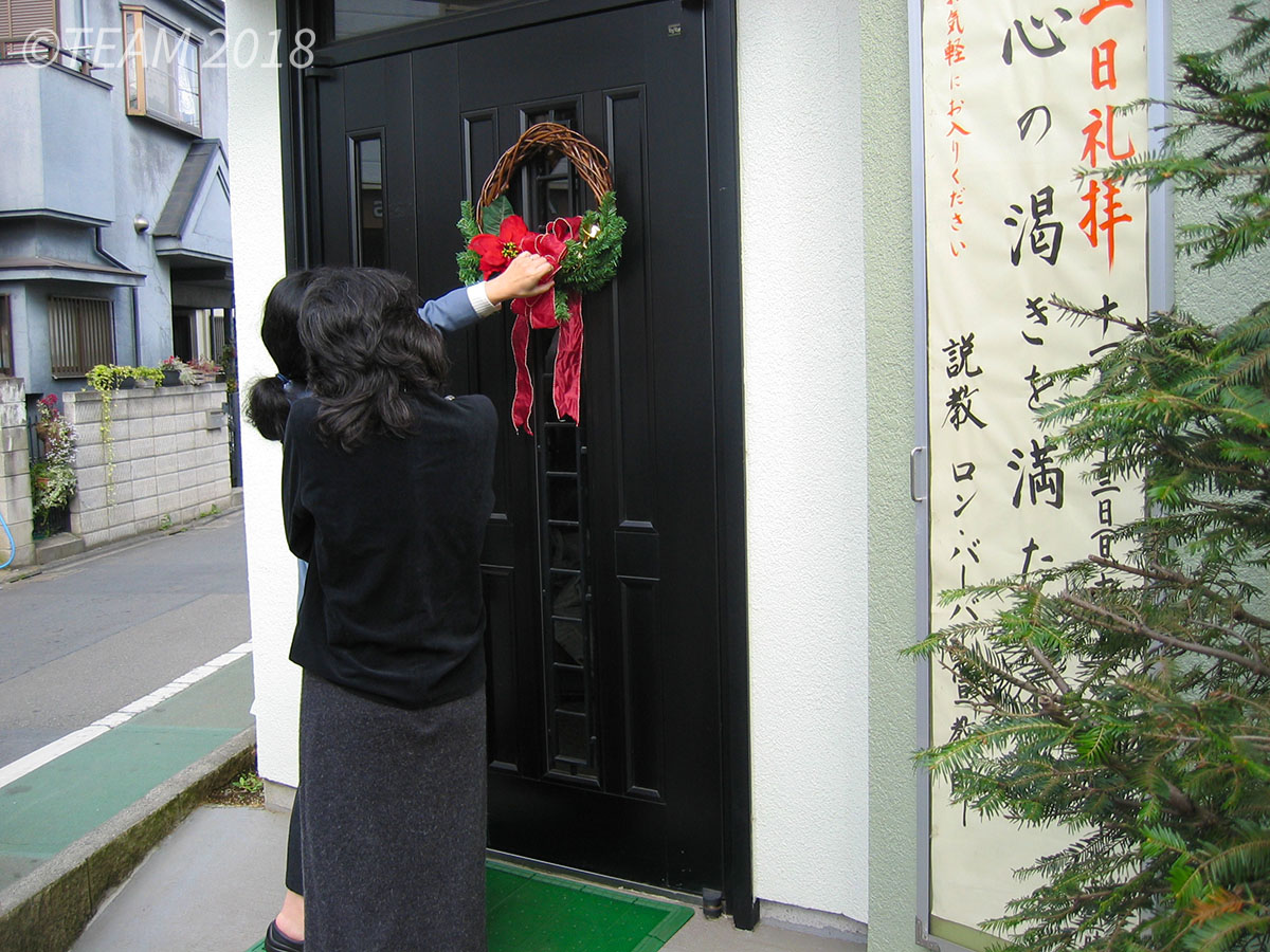 Two women hand a Christmas wreath on a door.