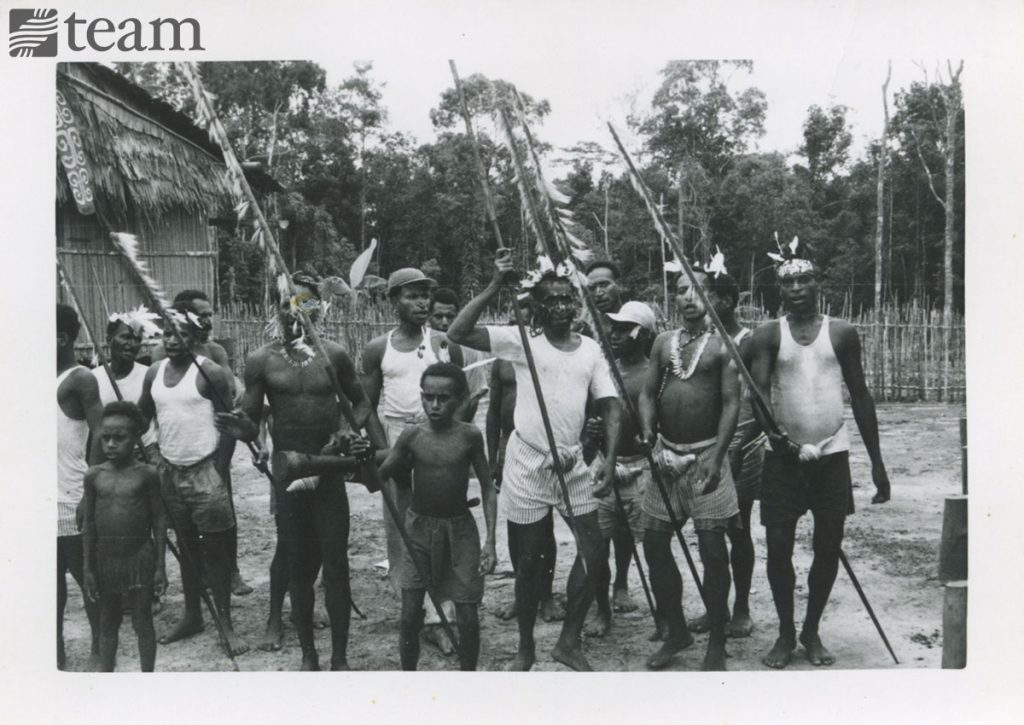 A group of papuan men pose with their weapons
