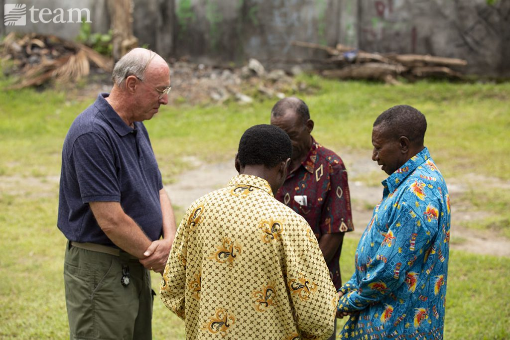 TEAM missionary Walter Kennedy prays with Yakobus and two other missionaries