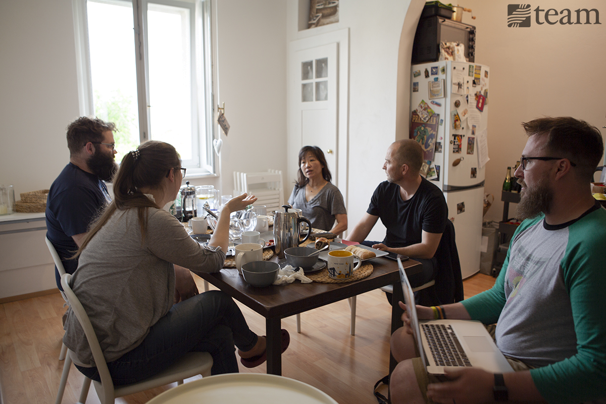 A group of people sit together over a meal to discuss their missions strategy