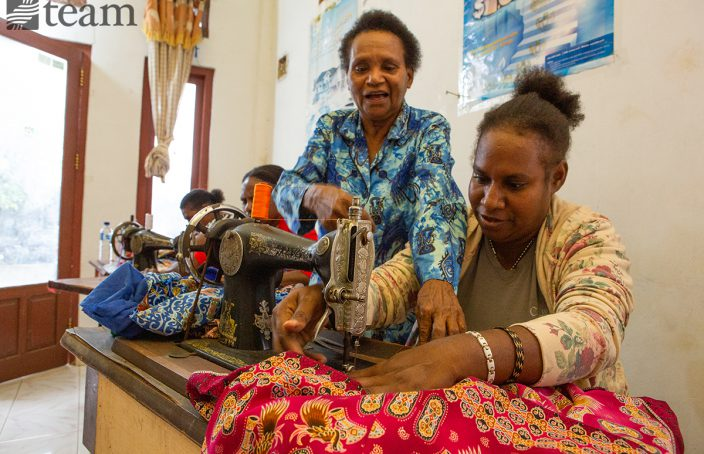 Marice teaches a woman to sew