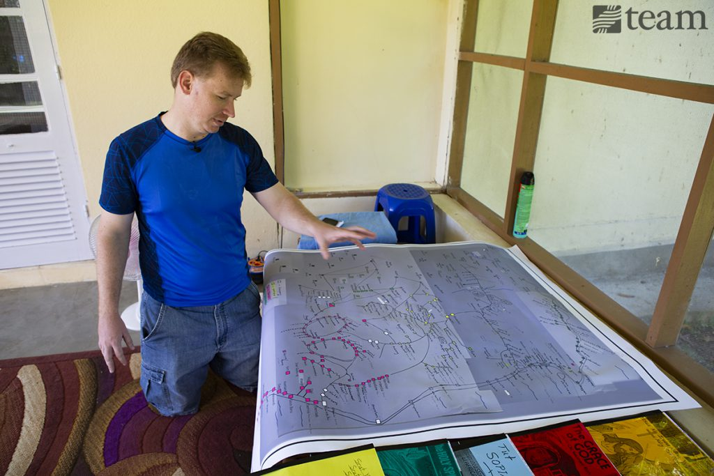 A missionary stands with a map of the tribes surrounding the Hatam tribe