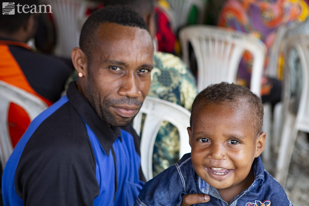 A Papuan man poses with his son
