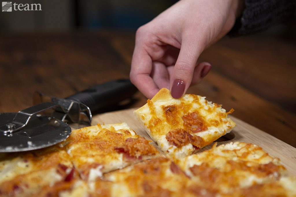 A woman grabs a slice of flammkuchen