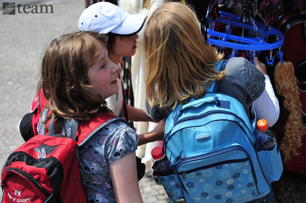 Two girls with backpacks have a conversation. Missionary kids on home assignment travel a lot.