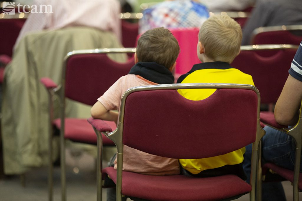 Two kids sit together in church