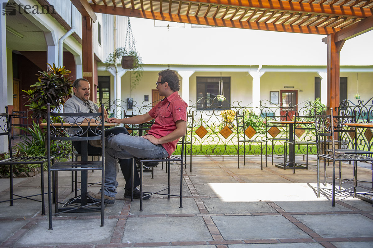 Two men sit outside at a table and talk. Feature photo: Preparing for missions during COVID-19