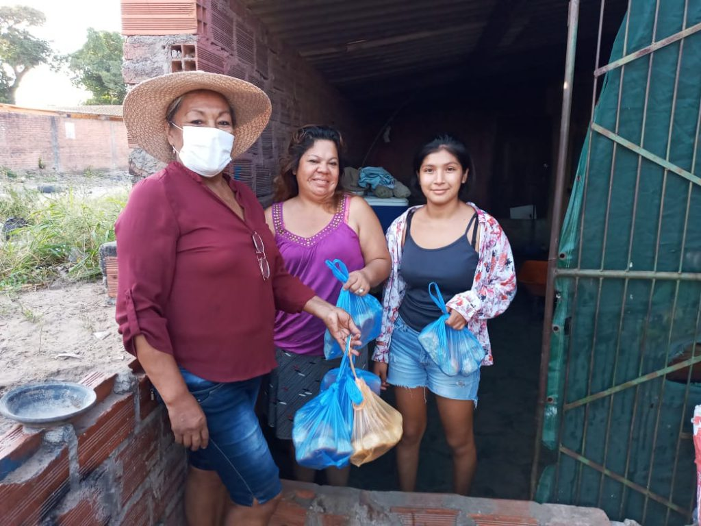 A local Christian give a bag of food to family as part of COVID-19 ministry