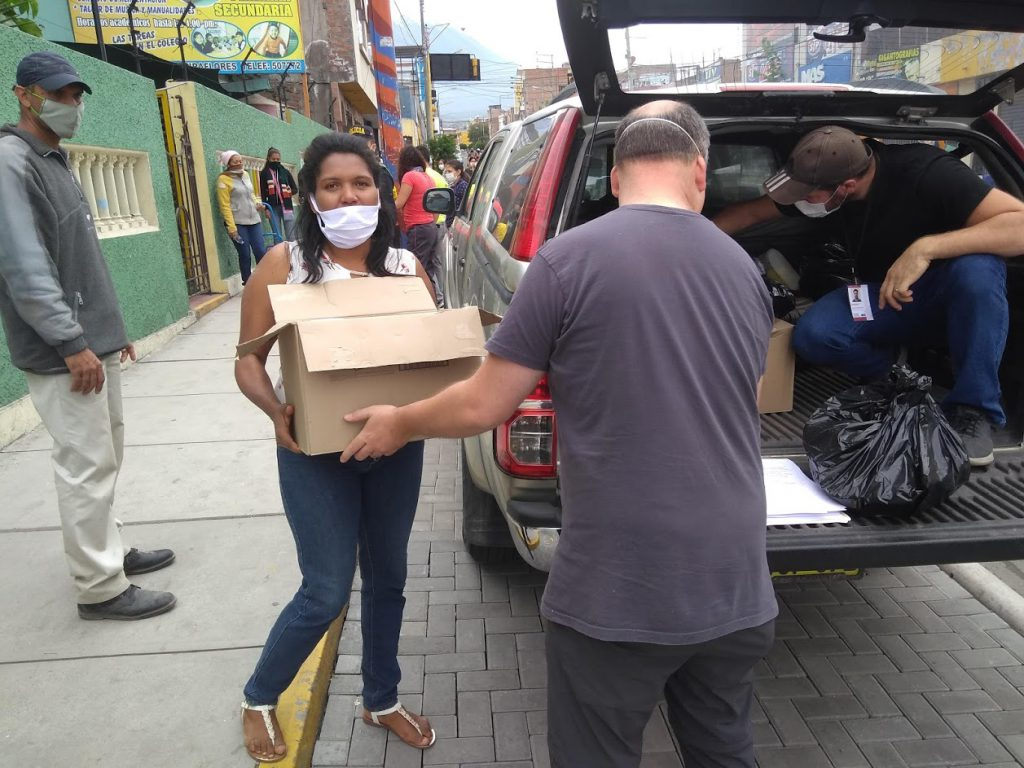 Workers unload boxes of food as part of COVID-19 ministry