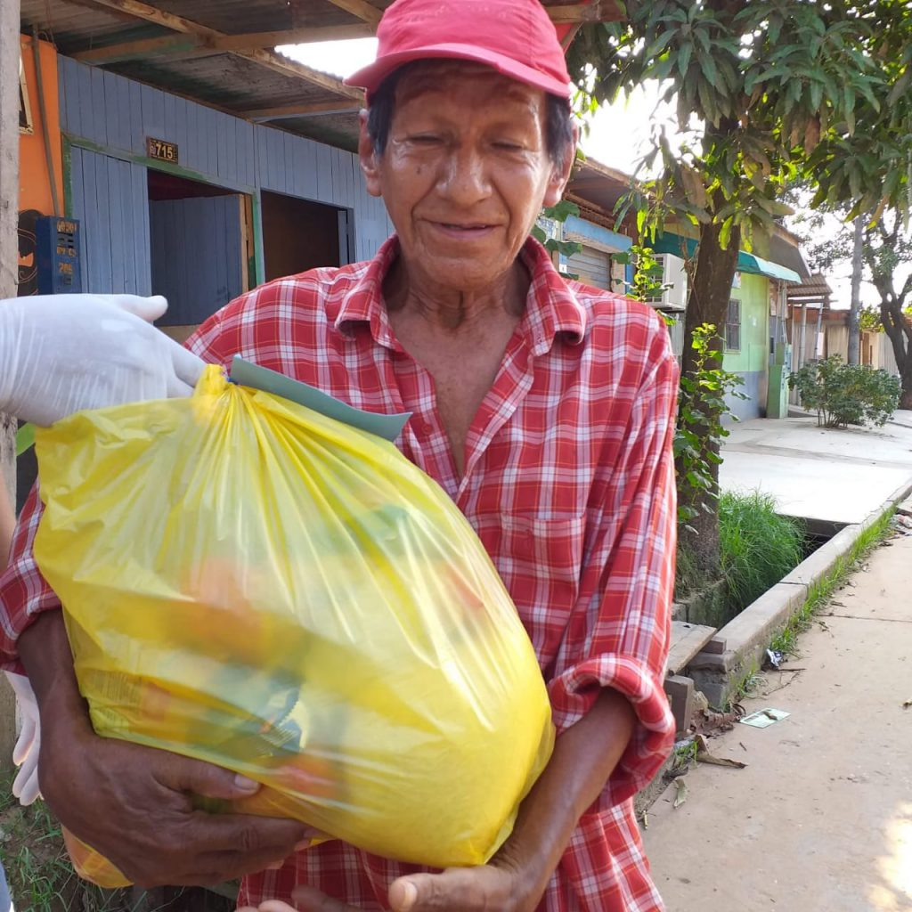 A man holds a large grocery bag he received as part of COVID-19 ministry