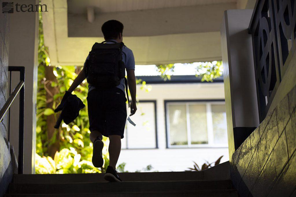 A man walks up a staircase